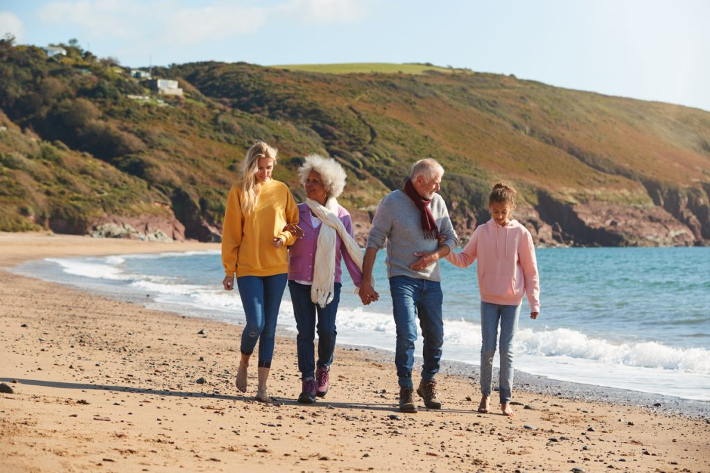 Multi-Generation Family Walking Along Shore On Winter Beach Vacation