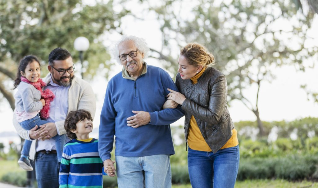 A multi-generation Hispanic family standing together outdoors in a park. The grandfather is in his 80s, standing arm in arm beside his adult daughter, in her 30s, and holding his grandson's hand. The boy is 6 years old and his sister is 4.